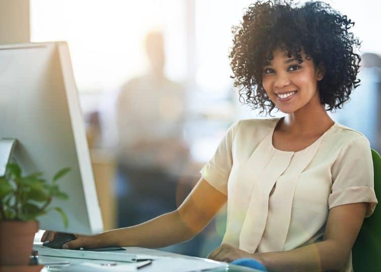 Smiling real estate appraiser working at her desk