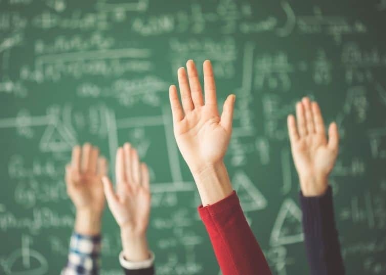 Students' hands raised in front of green chalkboard with appraisal math problems