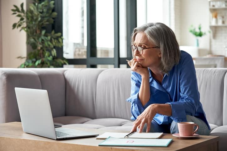 Mature woman watching professional development webinar on laptop computer