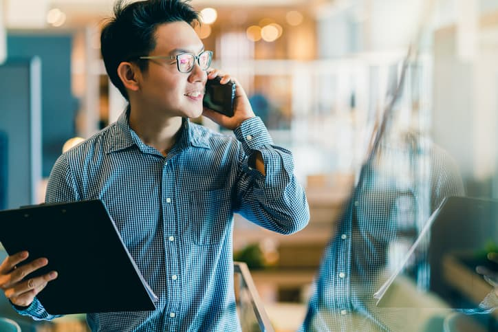 Smart, confident Asian appraisal business owner using smartphone working in office background
