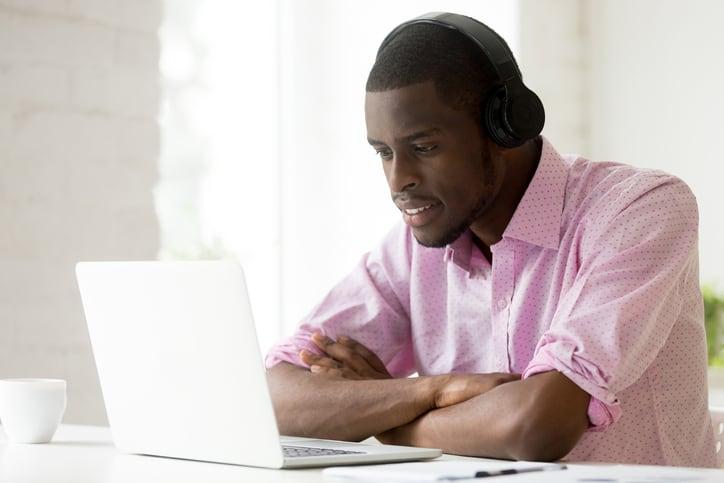 Young professional African American man wearing headphones, watching webinar