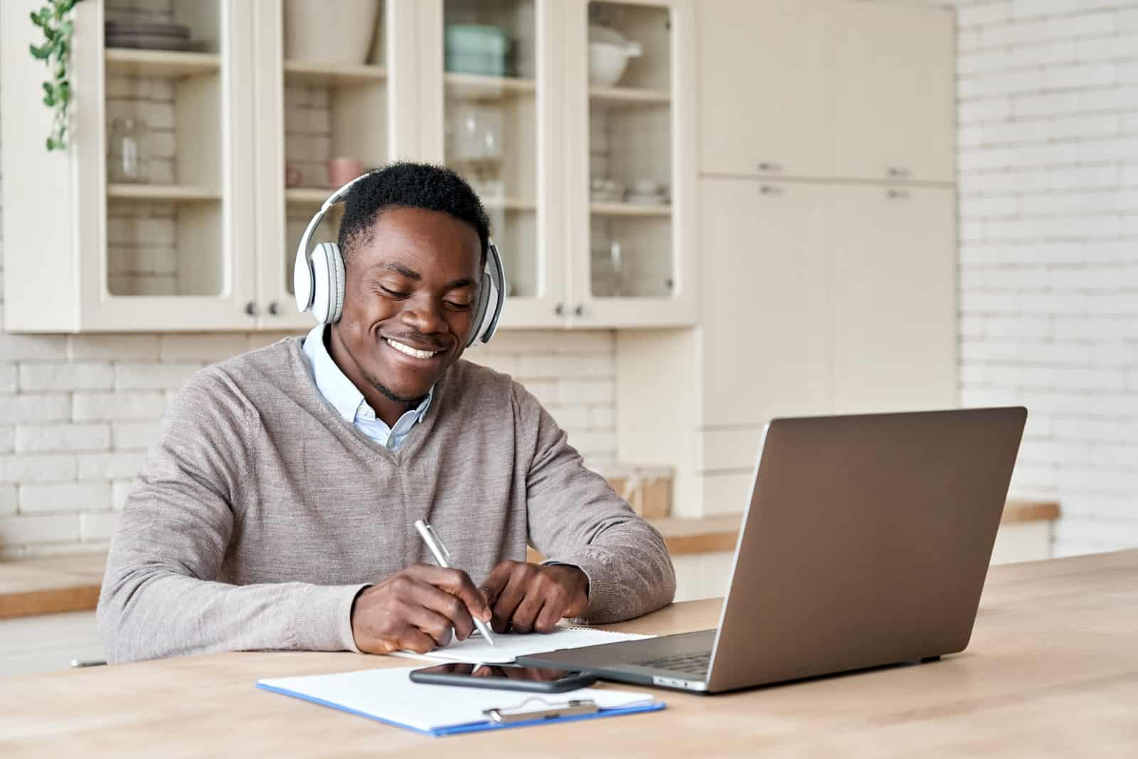 Happy african business man, student wearing headphones elearning on laptop computer sitting at kitchen table
