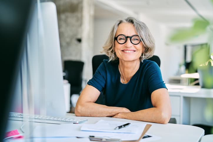 Portrait of confident mature female real estate appraiser working in a modern office