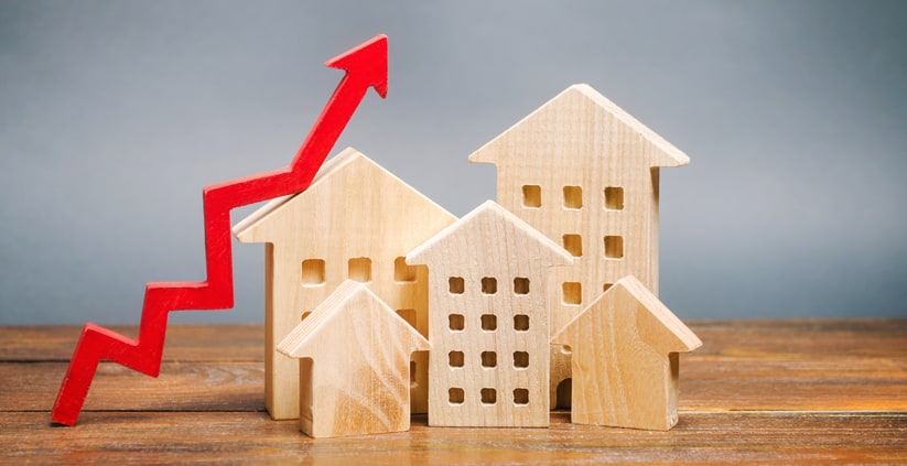 Miniature wooden houses and red arrow up, representing rising home prices and refinance volumes